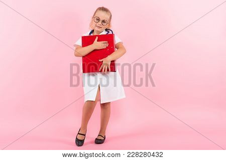 Portrait Of Little Girl Dressed Like Doctor In White Coat And Eyeglasses Wears Stethoscope And Holds