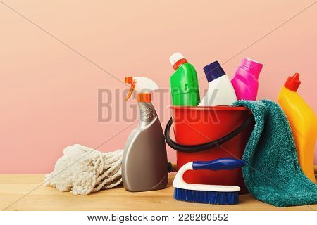 Variety Of House Cleaning Products On Wood Table At Pink Background, Closeup. Bucket, Brush, Rag, Mo
