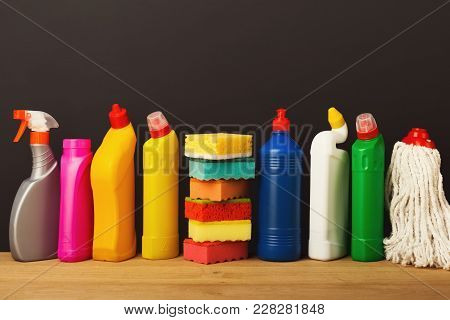 Group Of Colorful Cleaning Products On Dark Background. Different Bottles, Sponges And Mop On Wood T
