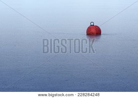 Red Buoy Frozen In Ice On The Blue Water In A Lake Or The Sea, Abstract Background For Winter Season