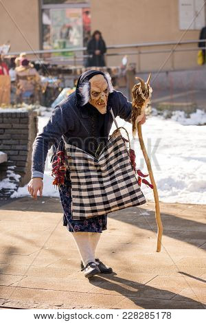 Pernik, Bulgaria - January 26, 2018: Young Man Dressed As Witch, Scary Mask And Wooden Rod Banishes