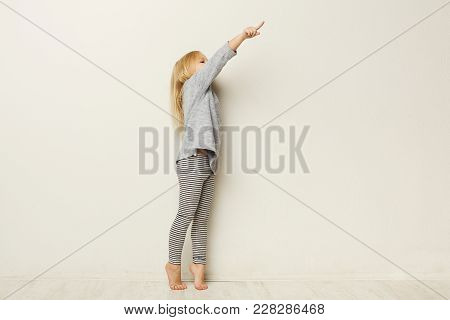 Full Length Portrait Of A Happy Little Girl Standing And Pointing Aside With Finger On White Studio