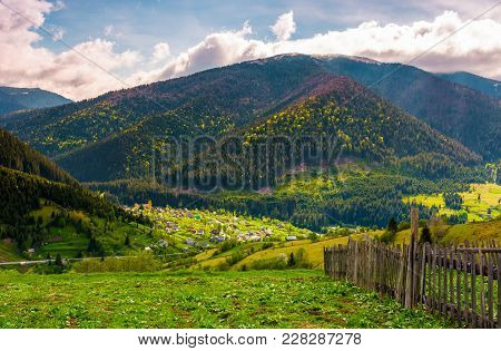 Village In Valley On A Cloudy Springtime Day. Fence On Hillside Above Beautiful Rural Area