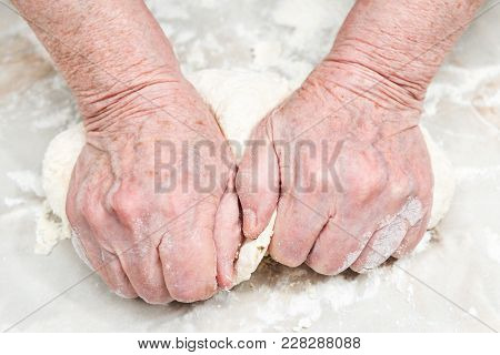 Female Senile Hands Knead The Dough On A Table, Close-up