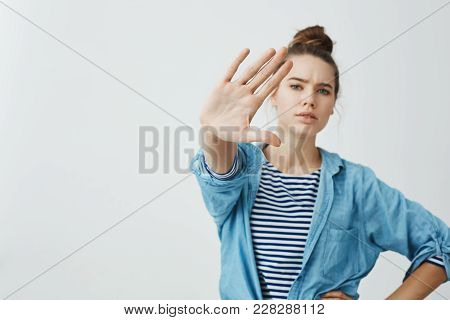 I Forbid You To Come Closer. Studio Shot Of Confident Serious Woman Pulling Hand Towards Camera In S