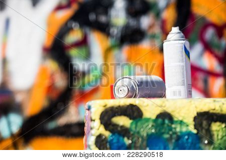 Used Paint Cans Near A Wall With Graffiti