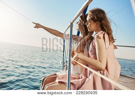 Two Attractive European Women Sitting At Bow Of Yacht, Looking At Something While Pointing At Seasid