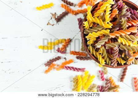 Colored Italian Fusilli Pasta In Bowl On White Wooden Table. Top View, Closeup.