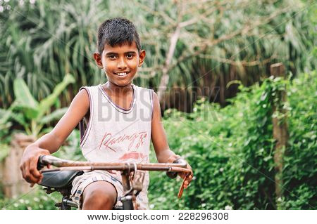 Weligama, Sri Lanka - December 21 , 2017: Little Barefoot Boy Stands Near The Old Rusty Bicycle And