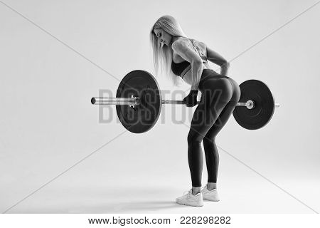 Black And White Photo Of Confident Young Woman Doing Weight Lifting Workout At Gym Turning Back Attr