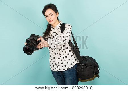 Portrait Of Young Attractive Woman Photographer In White Shirt Holding Camera And Bag Isolated On Bl