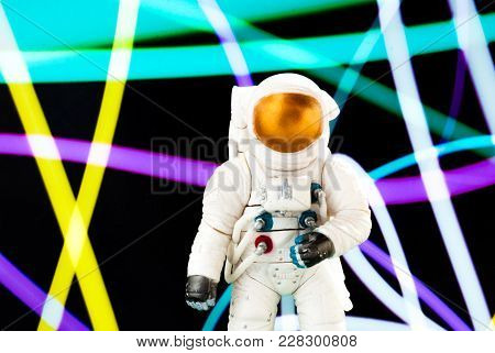 Toy Figure Of An Astronaut On The Background Of An Abstract Pattern