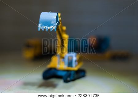 Bucket Of A Toy Excavator Close-up. Blurred Background With Transport Truck With Concrete Mixer