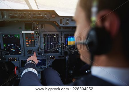 Close Up Pilot Arm Navigating Plane In Cabin. He Pressing Button. Instrument Concept