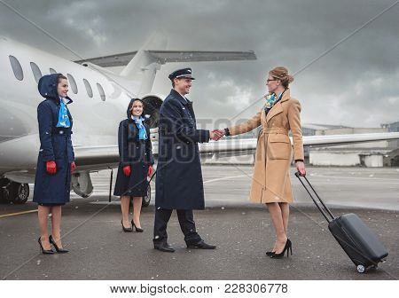 Full Length Outgoing Lady Greeting With Glad Pilot. Optimistic Air-hostesses Standing Near Aircraft.
