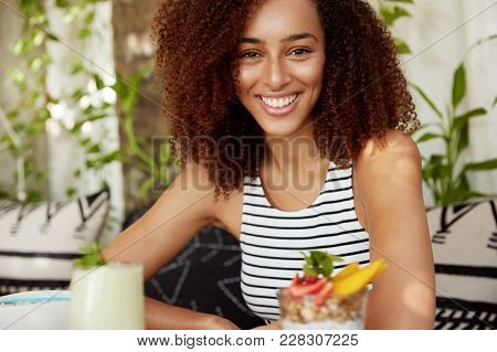 Positive African American Female With Curly Hair Enjoys Spare Time At Restaurant, Drinks Cocktail, H