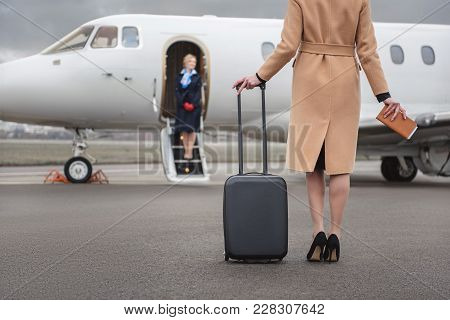 Female Going To Airplane While Holding Baggage In Hand. Happy Air-hostess Waiting For Her. Occupatio