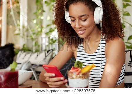 Dark Skinned Mixed Race Female In Stylish Headphones Downloads Audio Book On Mobile Phone, Spends Fr