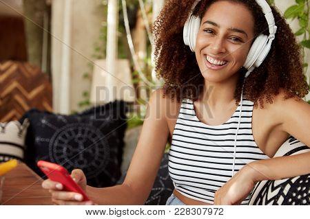 Happy Dark Skinned Woman Listens Favourite Song In Headphones, Chats Online On Smart Phone, Wears Ca