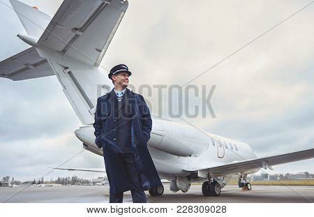 Low Angle Side View Cheerful Aviator Putting Hands In Pockets While Standing Opposite Aircraft. Prof