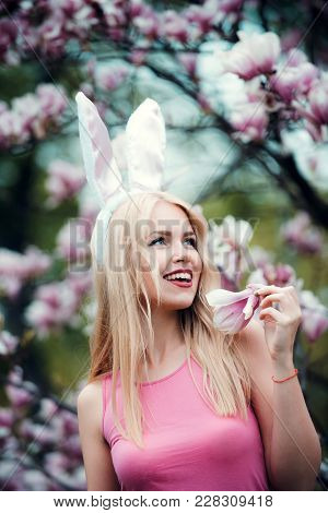 Woman Or Cute Girl Happy With Magnolia Flower With Pink, Bunny Ears On Long, Blond Hair In Rosy Top