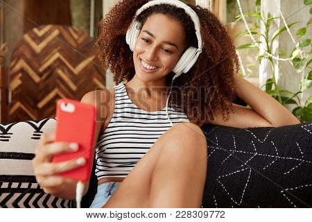 Portrait Of Happy Female Blogger Publishes New Photos On Website, Makes Selfie On Modern Smart Phone