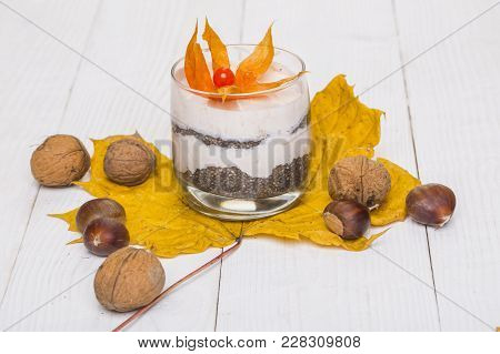Cream With Flower In Glass On Maple Leaf With Nuts. Food, Dessert, Snack On Wooden Background. Cuisi