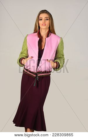 Fashion Photo Of A Beautiful Young Woman In A Pretty Dress With Jacket Over Grey Background. Fashion