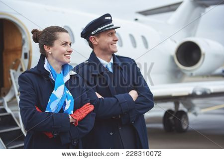 Side View Outgoing Young Stewardess And Beaming Aviator Looking Away While Situating Near Aircraft.