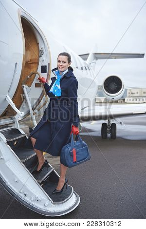 Full Length Portrait Of Smiling Stewardess With Luggage Standing On Stairs Near Aircraft. Occupation