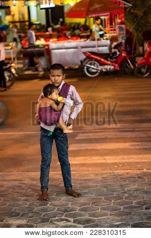Siem Reap, Cambodia- March 22, 2013: Unidentified Khmer Boy With A Baby In Cambodia. Khmer People Ar
