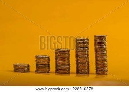 Euro Coins And Eurocents Stacked On A Yellow Background. Euro Money.  Currency Of The European Union
