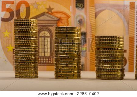 Stacked Euro Coins Against A Paper Denomination Worth Fifty Euros. Euro Money.  Currency Of The Euro