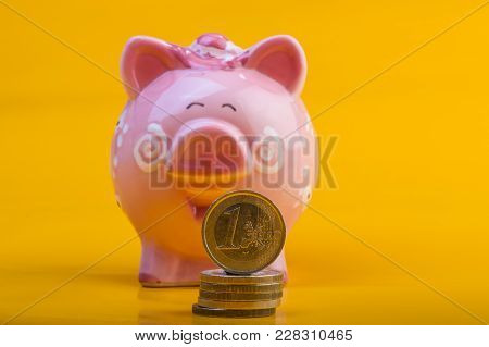 Piggy Bank And One Euro On A Pile Of Coins. Yellow Background. Cover. Euro Money. Currency Of The Eu
