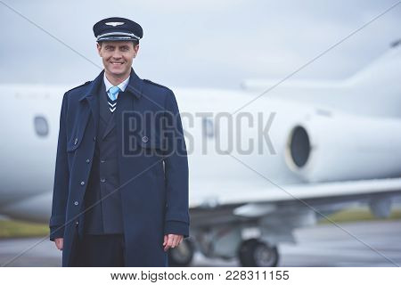 Portrait Of Beaming Aviator Standing At Airfield. He Looking At Camera. Job Concept. Copy Space