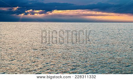 Dramatic Sunset Sky Over Sea. Sunbeams Passing Through Clouds. Sunset Over Calm Sea With Gentle Ripp