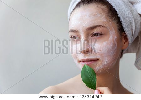 Beauty Portrait Of A Smiling Brunette Woman In A Towel On The Head With White Nourishing Mask Or Cre