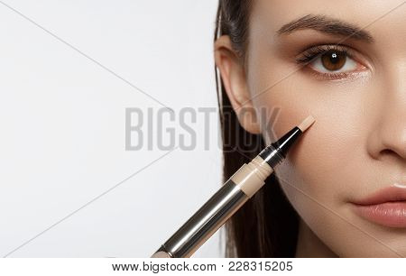 Close Up Of Half Female Face. Confident Young Woman Is Applying Concealer On Her Cheek. Isolated And