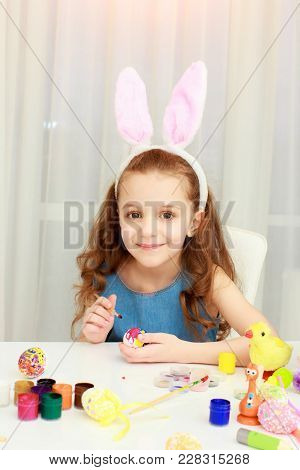 Portrait Of Little Girl In Easter Pink Bunny Ears Painting Easter Eggs. Little Girk In Easter Bunny