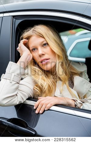 Bored Attractive Young Woman Sitting Waiting In A Car Staring Out Through The Open Window With A Glu