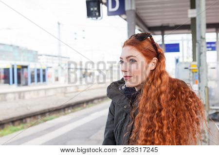 One Red Headed Young Female Commuter Wearing A Coat Waits With Her Hands Crossed At A Station For Th