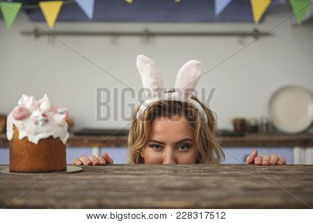 Attractive Young Female In Bunny Headband Peeking Out From Behind Kitchen Table And Looking At Camer