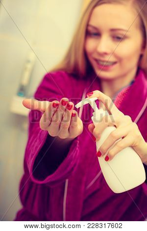 Body Care Concept. Woman Wearing Dressing Gown Applying Moisturizing Hand Cream On Hands And Nails A