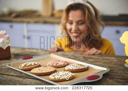 Glad Young Female Sitting At Kitchen Table And Looking At Delicious Glazed Cookies On Tray. Focus On
