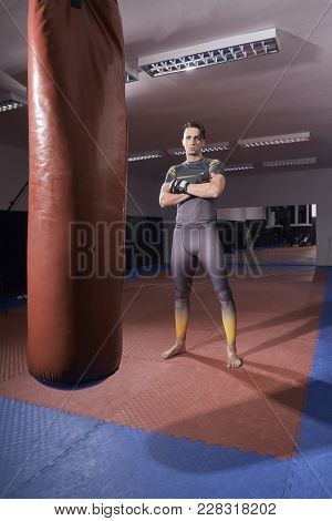 one young boxer standing posing, looking at camera. full lenght shot. indoors, punching bag.