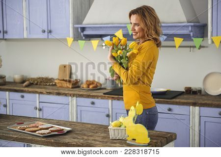 Side View Profile Of Happy Female With Yellow Flowers Standing In Country Style Kitchen And Smiling.