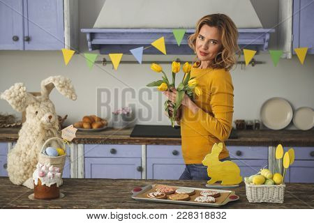 Waist Up Portrait Of Glad Beautiful Woman Standing In Festively Decorated Kitchen And Holding Bunch