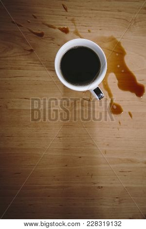Black Coffee In A White Cup Spilled On A Table