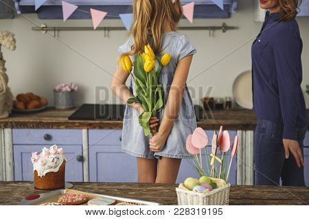 Young Girl Standing In Kitchen And Hiding Bunch Of Yellow Tulips Behind Her Back While Looking At He