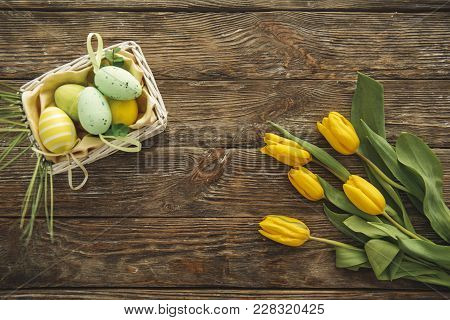 Top View Of Natural Tulips And Wicker Basket With Faberge On The Wooden Panel